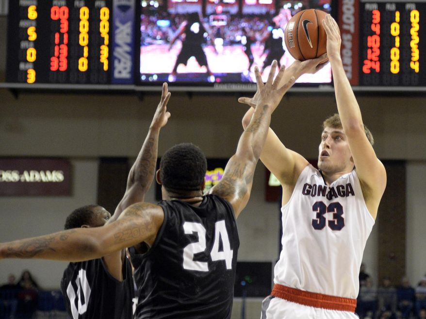 Gonzaga's Kyle Wiltjer shoots a 3-pointer as Loyola Marymount's Brandon Brown (10) and Shamar Johnson (24) defend during an NCAA college basketball game Wednesday, Dec. 23, 2015, in Spokane, Wash. (Jesse Tinsley/The Spokesman-Review via AP)