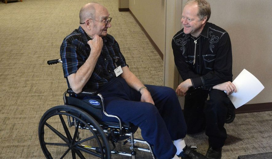 In this Dec. 3, 2015 photo, Floyd Beukelman, left, an 87-year-old resident of the Avera Prince of Peace retirement community in Sioux Falls, S.D., chats with Darrel Fickbohm before Fickbohm narrates Beukelman's memoirs to music. The program pairs seniors' memories with a performance by the Dakota Wind Quintent as part of the Music As Medicine program. (AP Photo/Dirk Lammers)