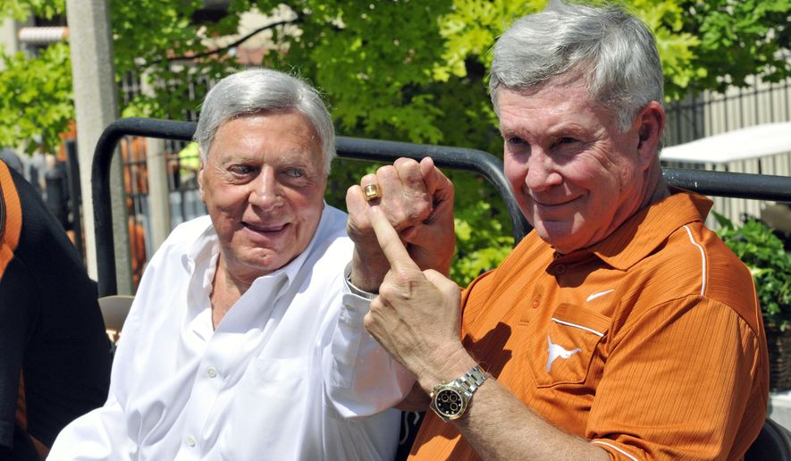 FILE - In this April 1, 2012 file photo, Texas coach Mack Brown, right, points to a Texas ring worn by attorney Joe Jamail before the Orange and White spring NCAA college football game, in Austin, Texas. Jamail, a swashbuckling, billionaire trial lawyer who toppled Texaco in court and so lavished the University of Texas with donations that his name adorns its iconic football field, has died at age 90. Spokesman Kevin Mortesen said Wednesday, Dec. 23, 2015 that UT Athletic Director Mike Perrin was informed of the death by a close family friend who was with Jamail Tuesday night. (AP Photo/Michael Thomas, File)