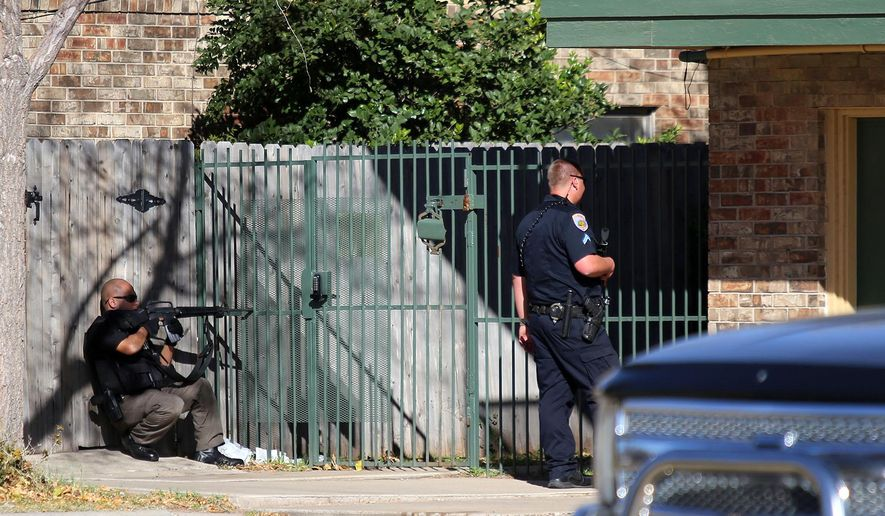 Officers wait outside an apartment complex on Wednesday Dec. 23, 2015, in Odessa, Texas. Authorities say multiple Odessa police officers have been shot while attempting to serve a warrant at the apartment complex, with the suspect barricaded inside. (Edyta Blaszczyk/Odessa American via AP) MANDATORY CREDIT