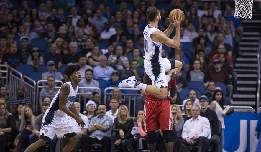 Orlando Magic forward Evan Fournier (10) shoots over the top of Houston Rockets guard Patrick Beverley (2) during the first half of an NBA basketball game in Orlando, Fla., Wednesday, Dec. 23, 2015. (AP Photo/Willie J. Allen Jr.)