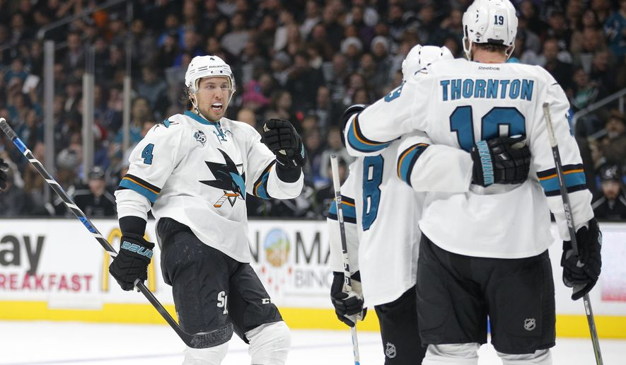 San Jose Sharks' Brenden Dillon, left, and Joe Pavelski celebrate a goal by Joe Thornton, right, during the first period of an NHL hockey game against the Los Angeles Kings, Tuesday, Dec. 22, 2015, in Los Angeles. (AP Photo/Jae C. Hong)