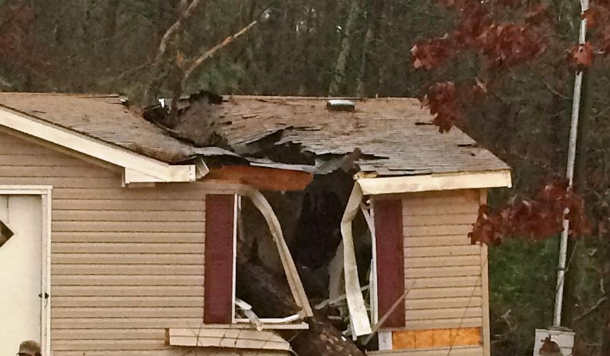 This photo provided by the Pope County Sheriff's Department shows a storm damaged home outside of Atkins, Ark., on Wednesday, Dec. 23, 2015. High winds and heavy rain caused a large tree to become uprooted and fall on the house resulting in the death of an 18-year-old woman and trapping her 1-year-old child inside, authorities said. Rescuers pulled the toddler safely from the home. (Pope County Sheriff's Department photo via AP)