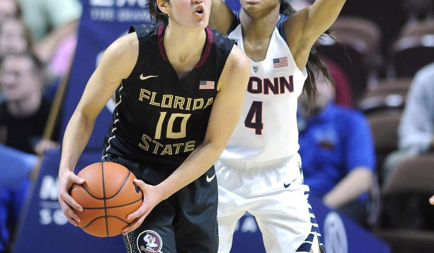 In this Dec. 11, 2015 photo, Florida State's Leticia Romero, left, is guarded by Connecticut's Moriah Jefferson during an NCAA college basketball game in Uncasville, Conn. Romero is one of 275 international players competing this season in women's Division I basketball. Nearly 50 different countries are represented, including Russia, Spain, Australia, Brazil, Senegal, Canada and China. (AP Photo/Fred Beckham)