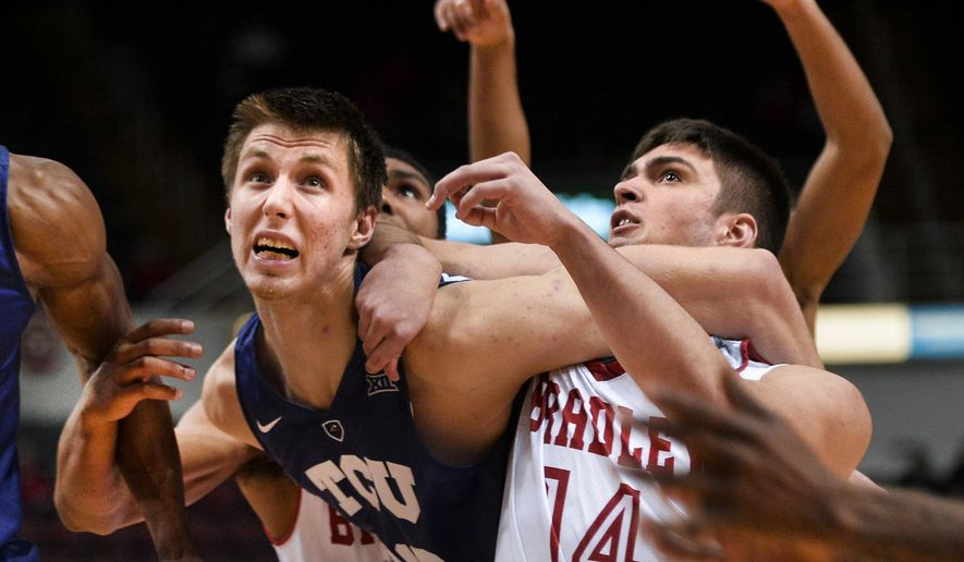 TCU's Vladimir Brodziansky, left,  gets tangled up with Bradley's Peter Hanley during an NCAA college basketball game at Carver Arena in Peoria, Ill., Wednesday, Dec. 23, 2015. TCU won 53-49. (Ron Johnson/Peoria Journal Star via AP)