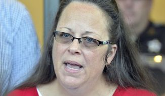 In this Sept. 14, 2015, file photo, Rowan County Clerk Kim Davis makes a statement to the media at the front door of the Rowan County Judicial Center in Morehead, Ky., when she announced that her office will issue marriage licenses under order of a federal judge, but will not have her name or office listed. (AP Photo/Timothy D. Easley, File)