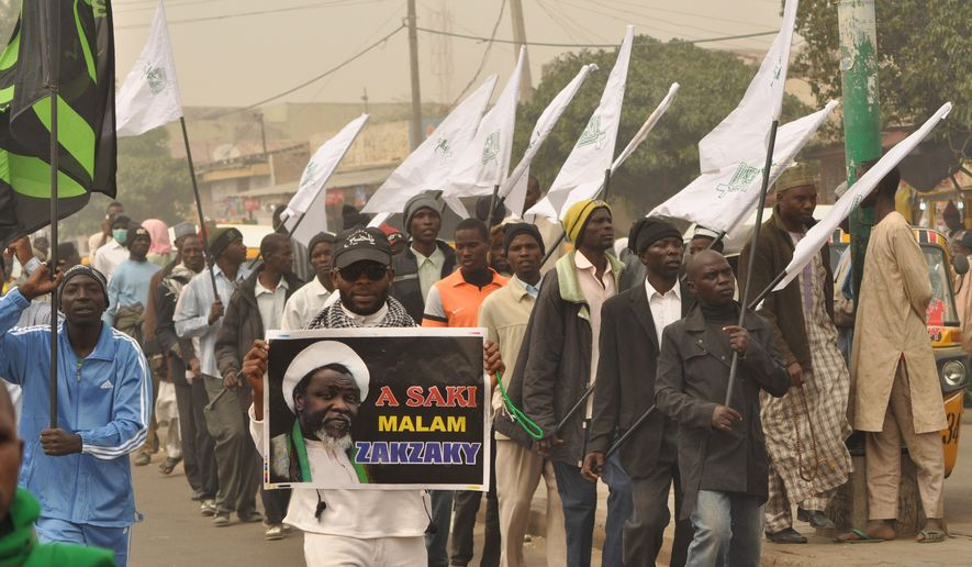 Nigeria Shiite Muslims hold religious flags and banners in a procession celebrating Prophet Muhammad's birthday and also demanding the release of Shiite leader Ibraheem Zakzaky, on posters, in Kano, Nigeria, Thursday, Dec. 24, 2015. (AP Photo/Muhammed Giginyu)