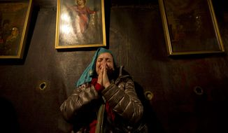 Christian pilgrims pray inside the Grotto of the Church of Nativity, traditionally believed by Christians to be the birthplace of Jesus Christ, in the West Bank town of Bethlehem on Christmas Eve, Thursday, Dec. 24, 2015. (AP Photo/Majdi Mohammed)