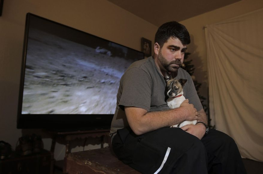 """In this photo taken Thursday, Dec. 17, 2015, Josh Redmyer, a former Marine who served three tours in Iraq, poses with Milo, who he calls his """"therapy dog,"""" in Oroville, Calif.  Redmyer, who was diagnosed with Post-Traumatic Stress Disorder in 2009,  received a less-than-honorable discharge in 2012. He is among the thousands of veterans who cannot receive veterans health benefits because of a less-than-honorable discharge. Redmyer turns to Milo, who is a birthday present from his roommate, when he becomes despondent. (AP Photo/Rich Pedroncelli)"""