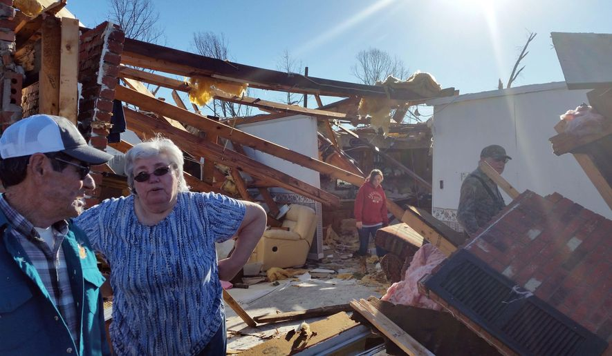 Charles and Daisy Johnson, of Benton County, Miss., left, survey the damage to their home, Thursday, Dec. 24, 2015. The couple were temporarily trapped in their shelter Wednesday as a severe winter storm rolled over their home. At least seven people were killed in Mississippi, Tennessee and Arkansas as spring-like storms mixed with unseasonably warm weather rolled through the South. (AP Photo/Phillip Lucas)