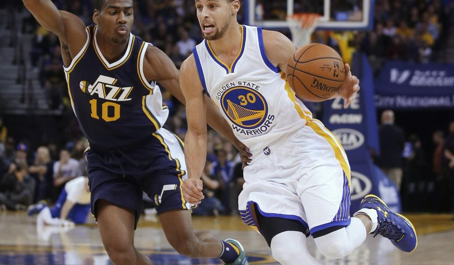 Golden State Warriors' Stephen Curry (30) dribbles past Utah Jazz's Alec Burks (10) during the first half of an NBA basketball game Wednesday, Dec. 23, 2015, in Oakland, Calif. (AP Photo/Marcio Jose Sanchez)