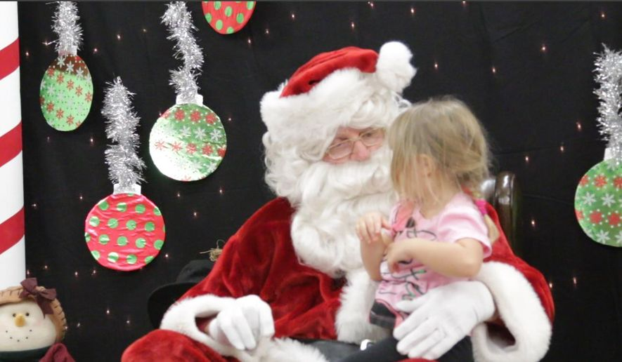 In this Tuesday, Dec. 22, 2015 photo, Randy Dallman talks to a girl as they pose for a photo in Kearney, Neb. Dallman of Franklin has been dressing up as Santa Claus and visiting the children of Franklin County for 55 years. (Tyler Jacobs/The Daily Hub via AP) MANDATORY CREDIT