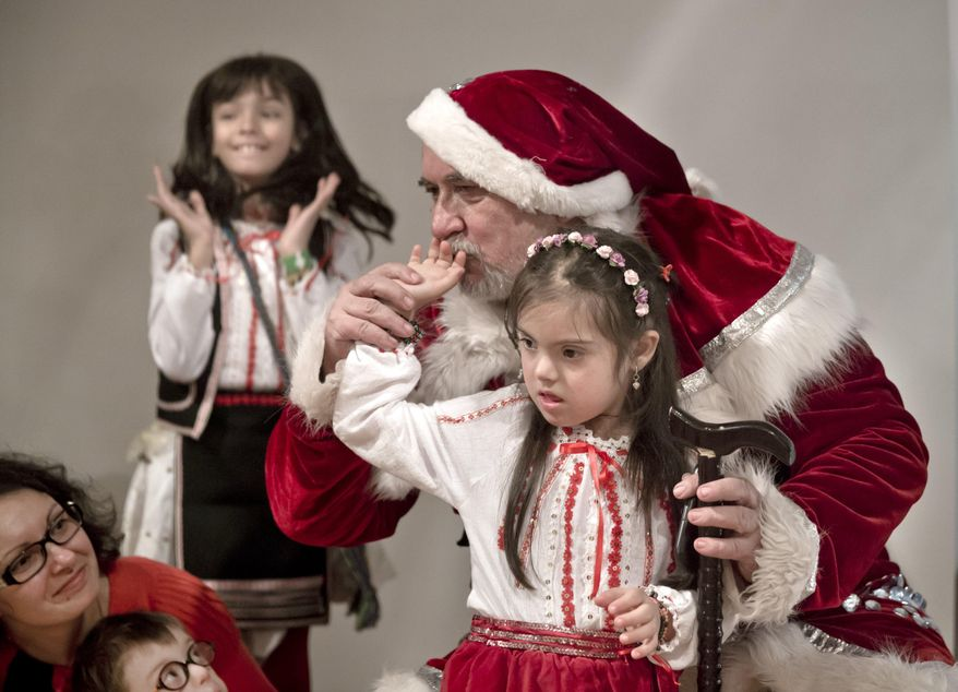 In this Friday, Dec. 18, 2015 image a man dressed as Santa Claus kisses the hand of a girl as another one reacts with joy during a Christmas party for children affected by the Down Syndrome, organized by the Angels Down Friends association in Bucharest, Romania. Angels Down Friends, founded in 2013 by the parents of a child with Down syndrome, organized the event to encourage parents of children with the condition and with the long-term goal of more fully integrating youngsters with Down into society. (AP Photo/Vadim Ghirda)