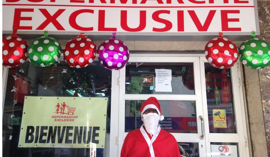 In this photo taken with a mobile phone on Thursday, Dec. 17, 2015, Mamadou Aliou Ba, , who dresses as Santa Claus poses for a photograph in front of a supermarket in Darkar, Senegal. After his morning prayers at the mosque, 25-year-old Mamadou Aliou Ba puts on his Santa suit, the padded belly protruding from his thin, tall frame, and goes to work. He stands proudly, smiling from behind a snowy white mustache and beard that take over his face, waving to families walking by the supermarket in one of Dakar's wealthier neighborhoods.  (AP Photo/Carley Petesch)