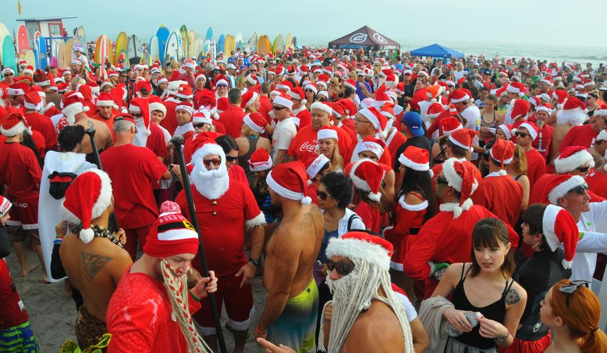 More than 6000 people showed up to watch hundreds of surfing Santas take to the waves in Cocoa Beach, Fla., Thursday, Dec. 24, 2015, at the end of Minutemen Causeway for the 7th Surfing Santas of Cocoa Beach.  The event raises money for Grind for Life. The event has grown since George Trosset and his son George and daughter-in-law Britteny went surfing in Santa, snowman and  elf costumes seven years ago. (Malcolm Denemark/Florida Today via AP)