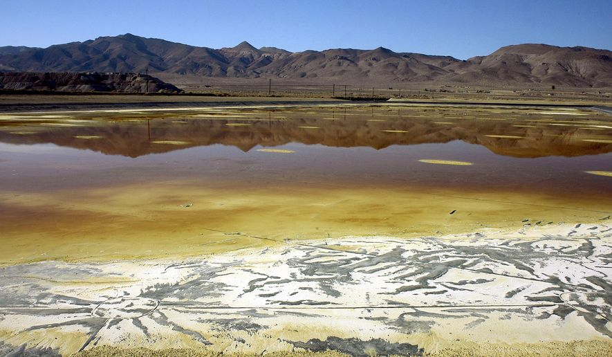 In this Nov. 30, 2004, file photo, an evaporation pond holds contaminated fluid and sediment at the former Anaconda copper mine near Yerington, Nev. Fifteen years after U.S. regulators started assessing the damage and health risks at a contaminated copper mine in Nevada, the Environmental Protection Agency wants to add the abandoned site to its Superfund National Priority List. (AP Photo/Debra Reid, File)