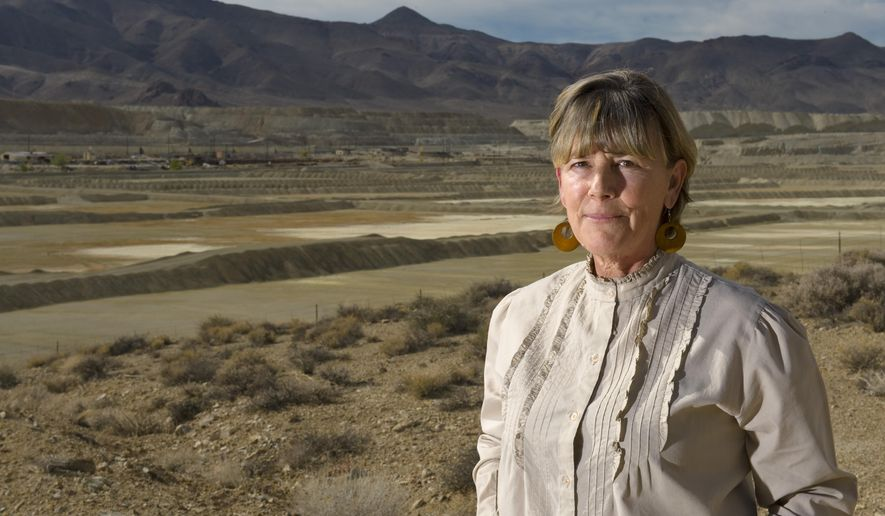 FILE - In this Oct. 26, 2009, file photo, Peggy Pauly, who formed Yearington's first citizen advocacy group to address the water contamination from the former Anaconda copper mine site near Yearington, Nev., is pictured in front of the leach ponds that are responsible for most of that contamination. Fifteen years after U.S. regulators started assessing damage and health risks at an abandoned Nevada copper mine, the Environmental Protection Agency is moving to add the contaminated site to its Superfund National Priority List, according to documents obtained by The Associated Press. (AP Photo/Scott Sady, File)