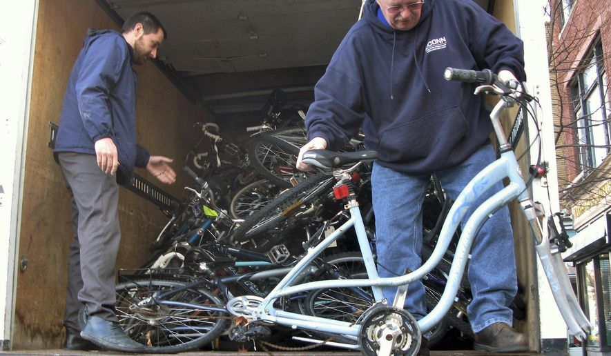 In this Dec. 10, 2015 photo, Nathan Bedard, left, and Ron Ethridge with the UConn facilities department, unload bicycles at the Center for Latino Progress in Hartford, Conn. The school says about 100 bikes a year are abandoned on campus. They are being donated to the center, which runs a program that allows people to repair one bike for a donation to a shelter and another to keep.  (AP Photo/Pat Eaton-Robb)