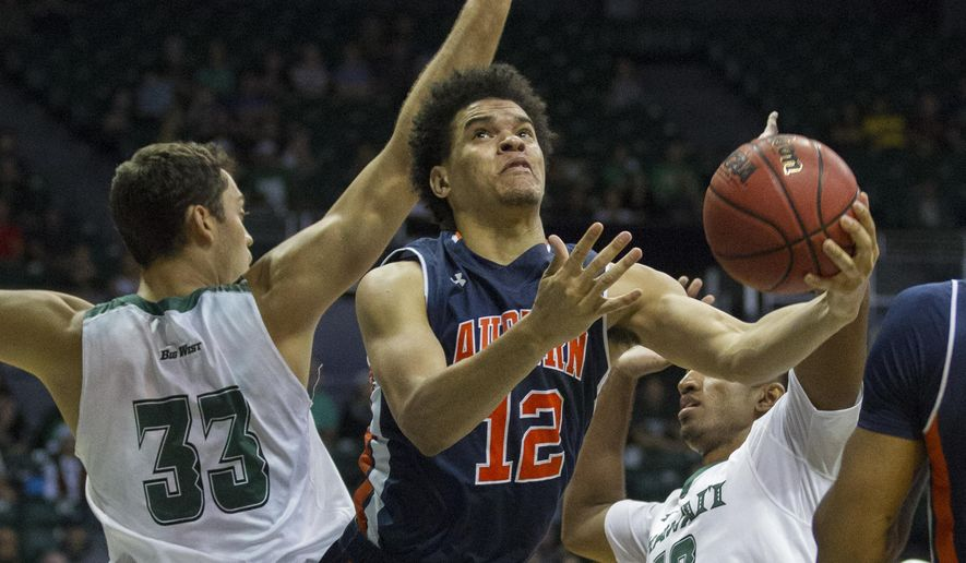 Auburn forward Tyler Harris (12) splits between Hawaii forward Stefan Jankovic (33) and guard Sai Tummala (12) to shoot a layup in the first half of an NCAA college basketball game at the Diamond Head Classic, Friday, Dec. 25, 2015, in Honolulu. (AP Photo/Eugene Tanner)