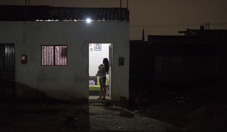 In this Dec. 22, 2015 photo, Angelica Pereira holds her daughter Luiza as she waits for her husband at their house in Santa Cruz do Capibaribe, Pernambuco state, Brazil. In the early weeks of Angelica Pereira's pregnancy, a mosquito bite began bothering her. At first it seemed a small thing. But the next day she awoke with a rash all over her body, a headache, a fever and a burning in her eyes. The symptoms disappeared within four days, but she fears the virus has left lasting consequences. (AP Photo/Felipe Dana)