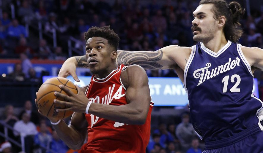 Chicago Bulls guard Jimmy Butler, left, goes to the basket ahead of Oklahoma City Thunder center Steven Adams (12) during the third quarter of an NBA basketball game in Oklahoma City, Friday, Dec. 25, 2015. Chicago won 105-96. (AP Photo/Alonzo Adams)