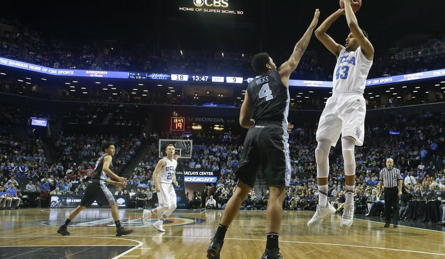 FILE - In this Dec. 19, 2015, file photo, UCLA's Jonah Bolden (43) shoots over North Carolina's Isaiah Hicks (4) during the first half of an NCAA college basketball game in New York. Shorter shot clocks and fewer timeouts. Less hand-checking and physical play. All rule changes implemented earlier this season designed to speed up the game of college basketball, encourage scoring and make it more aesthetically pleasing. (AP Photo/Frank Franklin II, File)