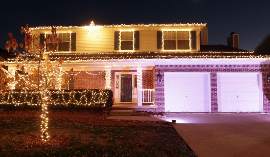 This photo taken on Dec. 15, 2015, shows the Wyndham Downs neighborhood home of Ryan and Kayla Jones with Christmas lights synchronized with Trans-Siberian Orchestra music which is broadcast on a low power FM frequency, in Lexington, Ky. (Pablo Alcala /Lexington Herald-Leader via AP) MANDATORY CREDIT