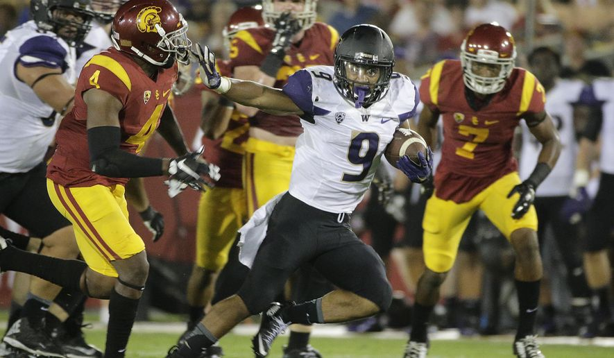 FILE - In this Thursday, Oct. 8, 2015, file photo, Washington's Myles Gaskin, center, carries the ball under pressure by Southern California's Chris Hawkins, left, during the second half of an NCAA college football game, in Los Angeles. Gaskin put in the finest season by a freshman in his school's history, rushing for 1,121 yards and 10 touchdowns after not fully taking over as the featured ball carrier until the fifth game of the season. Washington faces Conference USA runner-up Southern Miss on Saturday, Dec. 26, in the Heart of Dallas Bowl. (AP Photo/Jae C. Hong, File)