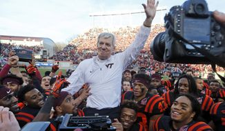 FILE - In this Saturday, Nov. 21, 2015, file photo, Virginia Tech head coach Frank Beamer is carried off the field by his players after an NCAA college football game against North Carolina, in Blacksburg, Va., in what was Beamer's last home game as coach since he is retiring at the end of the season. The legendary Virginia Tech head football coach will roam the sidelines for the final time when his Hokies (6-6) face Tulsa (6-6) in the Camping World Independence Bowl on Saturday, Dec. 26. (AP Photo/Steve Helber, File)