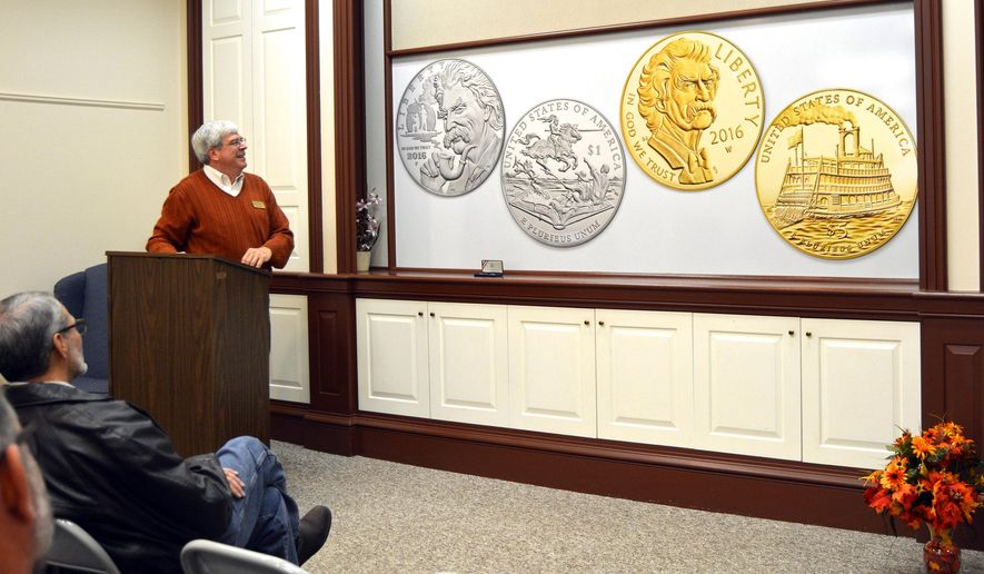 In this Nov. 30, 2015 photo, Henry Sweets, executive director of the Mark Twain Boyhood Home & Museum in Hannibal, Mo., unveils the design for commemorative gold and silver Mark Twain coins that will be sold starting next year. Some of the proceeds of the coin sales benefit four Twain-related sites, including the Hannibal home and museum. (Laken McDonald/Hannibal Courier-Post via AP) MANDATORY CREDIT