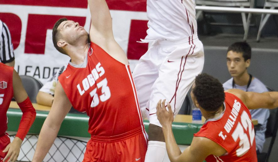 Washington State center Valentine Izundu, right, dunks over New Mexico center Nikola Scekic (33) as forward Tim Williams (32) looks on in the first half of an NCAA college basketball game at the Diamond Head Classic, Friday, Dec. 25, 2015, in Honolulu. (AP Photo/Eugene Tanner)