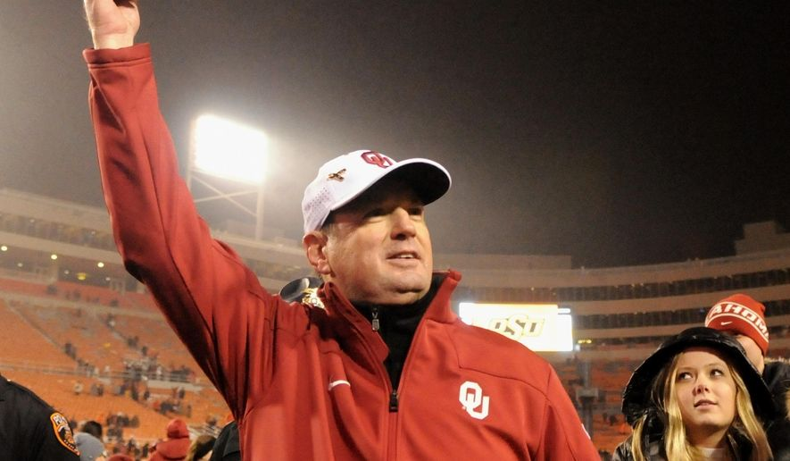 FILE - In this Nov. 28, 2015, file photo, Oklahoma head coach Bob Stoops holds up a Big 12 Champions hat following a 58-23 win over Oklahoma State in an NCAA college football game in Stillwater, Okla. The Sooners wisely stuck with Stoops as their head coach, even when many in this what-have-you-done-for-me-lately world questioned whether he was the guy to lead them back to the promised land. Now, the Sooners are Big 12 Conference champions and two wins away from a national championship. (AP Photo/Brody Schmidt, File)