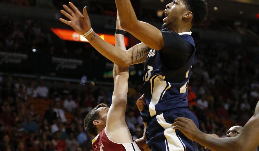 New Orleans Pelicans' Anthony Davis (23) shoots the ball against Miami Heat's Goran Dragic (7) during the first half of an NBA basketball game, Friday, Dec. 25, 2015, in Miami. (AP Photo/Joel Auerbach)