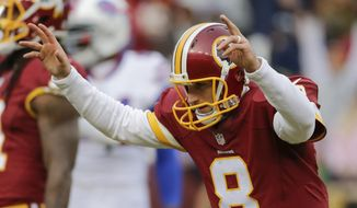 FILE - In this Dec. 20, 2015, file photo, Washington Redskins quarterback Kirk Cousins (8) celebrates wide receiver Pierre Garcon's touchdown during the second half of an NFL football game against the Buffalo Bills in Landover, Md. Redskins play the the Philadelphia Eagles on Saturday, Dec. 26, in Philadelphia. (AP Photo/Mark Tenally, File)