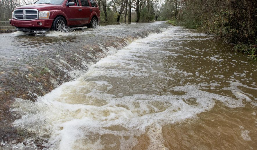 A vehicle drives along a flooded section of Hayneville Road in west Montgomery, Ala., on Christmas morning Friday, Dec. 25, 2015. The line of springlike storms continued marching east Thursday, dumping torrential rain that flooded roads in Alabama and caused a mudslide in the mountains of Georgia. (Mickey Welsh/The Montgomery Advertiser via AP) MANDATORY CREDIT