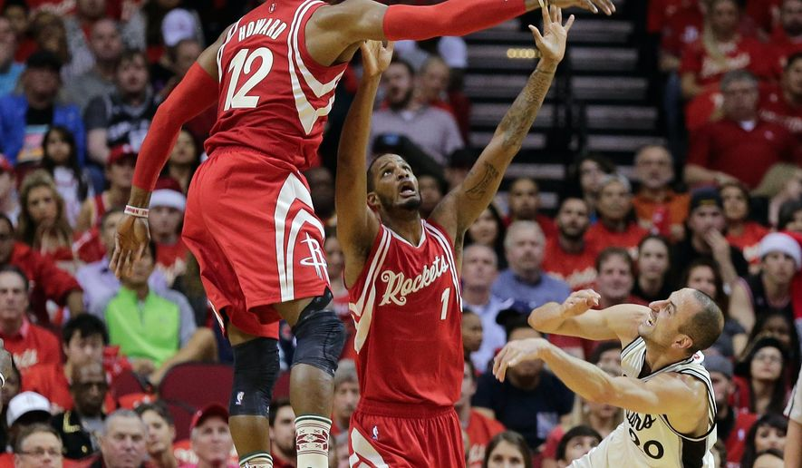 San Antonio Spurs guard Manu Ginobili (20) is fouled by Houston Rockets forward Trevor Ariza (1) as center Dwight Howard (12) blocks his shot attempt in the first half of an NBA basketball game Friday, Dec. 25, 2015, in Houston. (AP Photo/Bob Levey)