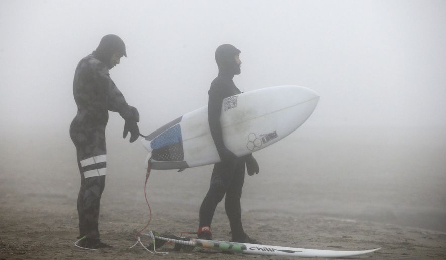 Enveloped by dense fog, two surfers prepare to enter the Atlantic Ocean from Rockaway Beach on Christmas Day, Friday, Dec. 25, 2015, in New York. With temperatures well above normal for this time of year, and tides higher than they've been in a while, surfers said conditions were ideal and they planned to take advantage of the unusually warm weather. (AP Photo/Kathy Willens)
