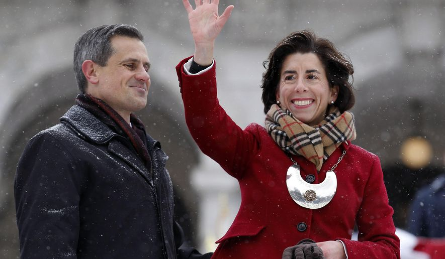 FILE - In this Jan. 6, 2015, file photo, Rhode Island Gov. Gina Raimondo, right, waves to the crowd beside her husband, Andy Moffit, following the gubernatorial inauguration on the steps of the Statehouse in Providence, R.I. Raimondo's election as the first female governor of Rhode Island was among the state's top stories in 2015. (AP Photo/Stew Milne, File)