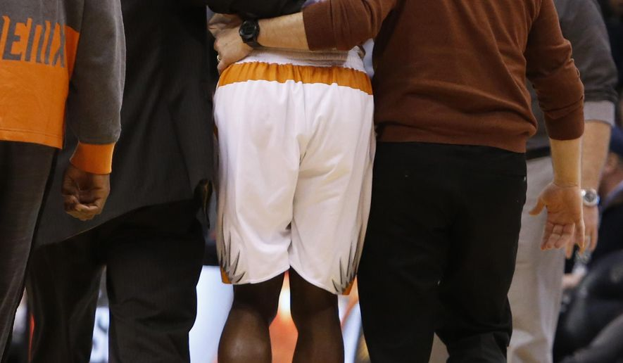 Phoenix Suns guard Eric Bledsoe (2) is helped off the court in the second quarter during an NBA basketball game against the Philadelphia 76ers, Saturday, Dec. 26, 2015, in Phoenix. (AP Photo/Rick Scuteri)