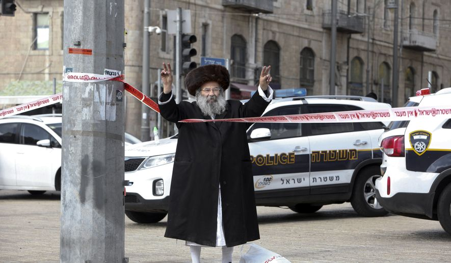 An ultra Orthodox Jew flashes victory signs at the scene of an alleged stabbing attack in Jerusalem Saturday, Dec. 26, 2015. According to a police spokeswoman, policemen approached a man who drew their suspicions just outside the Old City for following a pair of Jewish worshippers. Then he pulled out a knife and tried to stab one of them, officers opened fire and killed the assailant. (AP Photo/Mahmoud Illean)