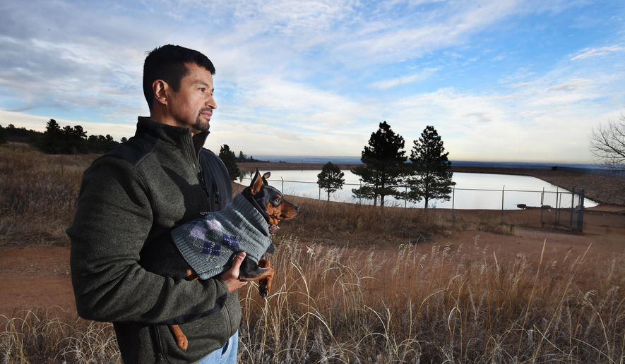 ADVANCED FOR RELEASE SATURDAY, DECEMBER 26, 2015  Jose Quiros often takes his dog, Hercules, for a walk in the Stratton Open Space, an area that has lots of memories for him. It is an area where his wife, Ksenia Quiros, loved to spend time and the place where she died last April. Quiros was missing for three days before her body was found, only a couple of weeks after her cadet son, Alexandre Quiros, died at the Air Force Academy of an apparent suicide. Quiros was standing in an area with a memorial bench will be placed near a reservoir in the open space on Wednesday, Nov. 26, 2015. Two benches will bookend the reservoir fin memory of both Ksenia and Alexandre. (Jerilee Bennett/The Gazette via AP)