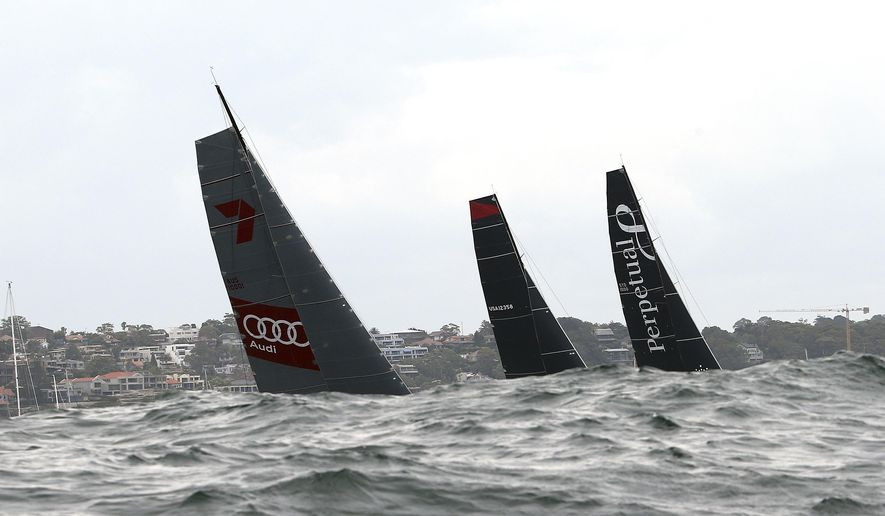 The sails of Wild Oats, left, Comanche, center, and Perpetual Loyal are seen as they sail out of the heads at the start of the Sydney Hobart yacht race in Sydney, Saturday, Dec. 26, 2015. The 628-nautical-mile race started in Sydney Harbour and is expected to end two to three days later in Hobart, the capital of the island state of Tasmania. (AP Photo/Rob Griffith)