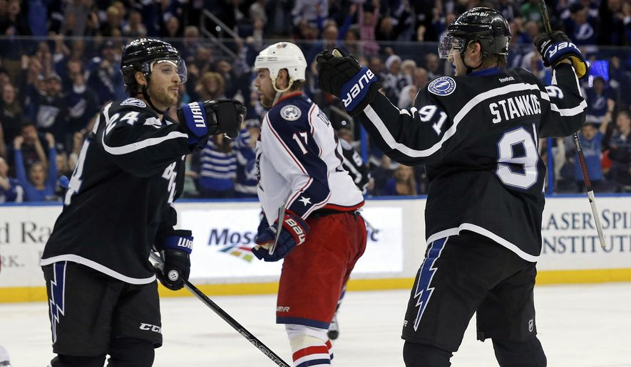 Tampa Bay Lightning's Steven Stamkos, right, celebrates his second goal of the game with teammate Ryan Callahan as Columbus Blue Jackets' Brandon Dubinsky reacts during the second period of an NHL hockey game Saturday, Dec. 26, 2015, in Tampa, Fla. (AP Photo/Mike Carlson)