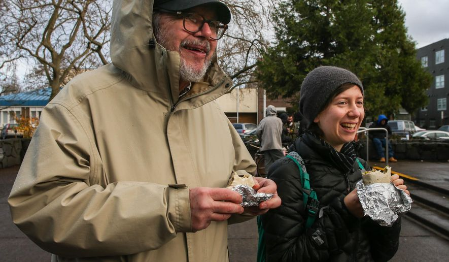 In this Dec. 20, 2015, photo, Ken Neubeck, left, and Tessa Barker take a break from volunteering with the Occupy Medical Group to enjoy a burrito from the Burrito Brigade in Eugene, Ore. A group of roughly 20 to 40 people get together each Sunday to cook, assemble and hand out homemade vegan burritos to homeless and hungry residents in Eugene and Springfield. (Mary Jane Schulte/The Register-Guard via AP) MANDATORY CREDIT