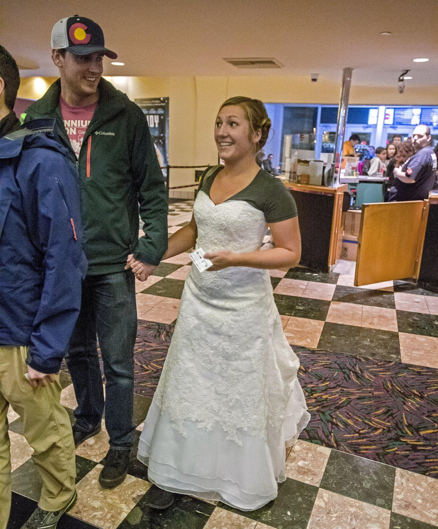 Kelsey and James Beil stand in the lobby of AMC Lakewood Mall 12 movie theater to see the latest Star Wars installment, Dec. 19, 2015.  She's wearing her wedding dress and a Star Wars tee shirt to keep her promise regarding a Facebook fund-raising challenge. (Peter Haley/The News Tribune via AP)