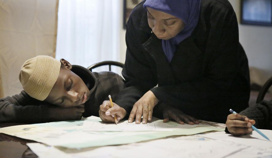 Xavier Johnson, left, and his mother, Aisha Johnson, draw in the living room of their Philadelphia home Nov. 6, 2015. ( Elizabeth Robertson/The Philadelphia Inquirer via AP)
