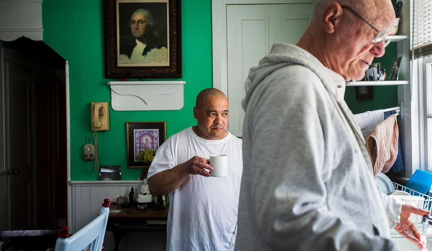 In this March 18, 2014 photo, John Mulligan, known by his Buddhist name Sivali, 76, right, and Angel Correa, known by his Buddhist name, Rahula, 42, appear in the kitchen at Bodhi House in Mount Joy Township, Pa. Mulligan has dedicated himself to teaching Buddhist practice at South Woods State Prison in New Jersey. (Shane Dunlap/The Evening Sun via AP)