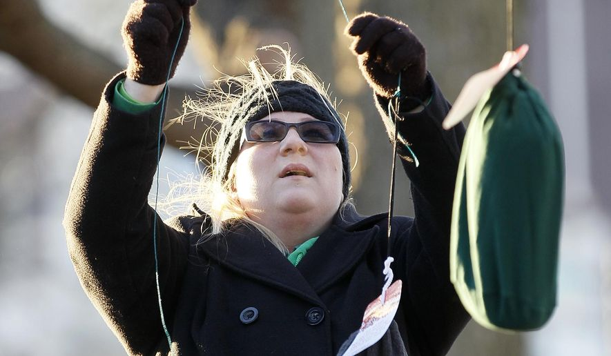 In this Dec. 17, 2015 photo, Candace Rogers, with Taking Back Waterloo, hang bags containing gloves, mittens and scarves in Lincoln Park for those in need in Waterloo, Iowa. The donated items hang by string from branches, or are tied onto tree trunks or draped over park benches. (Brandon Pollock/The Waterloo Courier via AP)