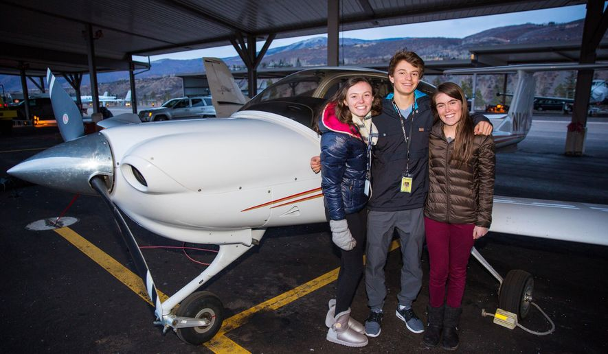 ADVANCE FOR SATURDAY, DEC. 26 - In this Friday, Dec. 11, 2015, photo, from left, Aspen High School students Juliette Woodrow, Ethan Burkley and Grace Ferguson pose in Aspen, Colo. Ferguson is setting new heights for herself and the high school's aerospace and aviation program as the first female to solo her own flight. (Jeremy Wallace/The Aspen Daily News via AP)