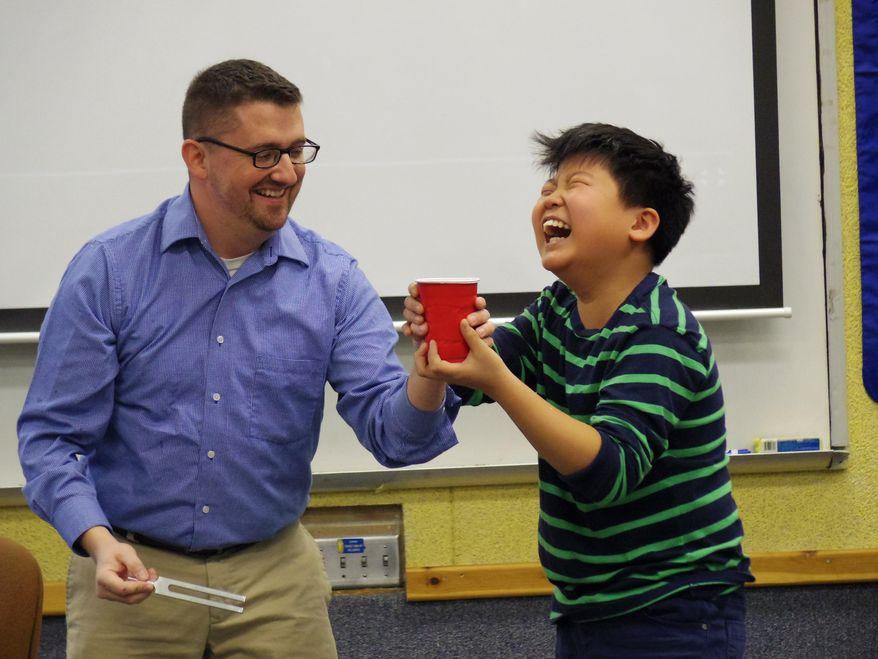 ADVANCE FOR THE WEEKEND OF DEC. 26 - In this Wednesday, Dec. 16, 2015 photo, Horizon Middle School teacher Michael Heuertz, who will be deployed in January to the Middle East, shares a laugh with sixth-grader Seth Choi during a lesson on sound vibration at the school in Kearney, Neb. (Josh Moody/The Daily Hub via AP) MANDATORY CREDIT